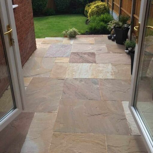 Autumn brown sandstone paving laid in patio leading from house to garden