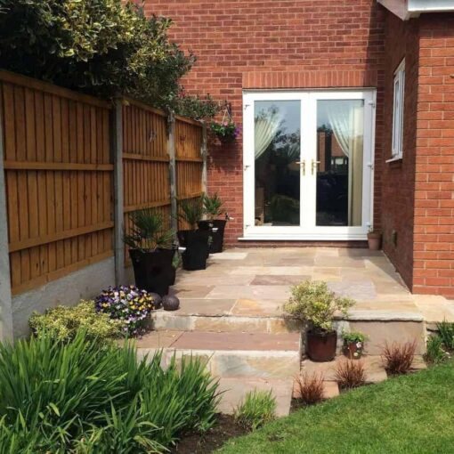 Garden patio paved with autumn blend sandstone leading to french doors at back of house
