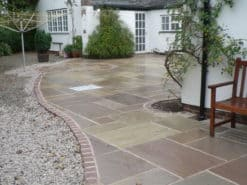 Damp Raj green sandstone laid in patio at side of house