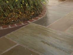 Raj green sandstone patio pack laid beside house
