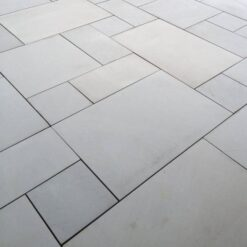 Patio pack of grey sawn sandstone paving laid in garden