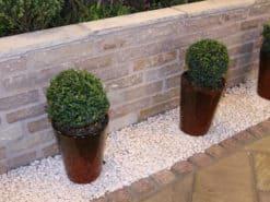 Garden wall made from raj green walling beside driveway