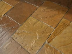 Square slabs of golden brown sandstone laid in patio
