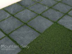 Square paving slabs of Mountain grey porcelain laid beside grass