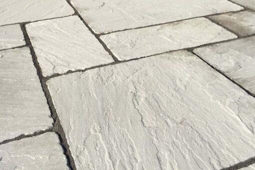 Closeup of mixed size tumbled Kandla grey paving slabs