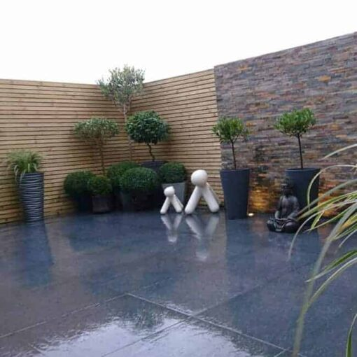 London black porcelain laid in walled garden patio with various plants and statues
