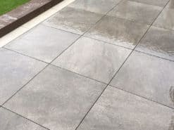 Square slabs of London graphite paving laid in garden patio