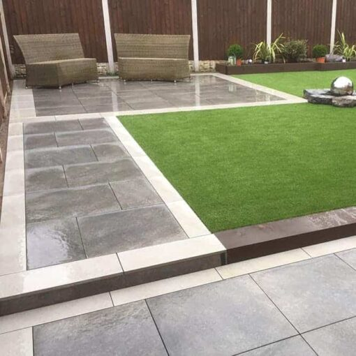 Path leading to a small garden patio seating area utilising London graphite porcelain