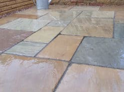 Wet tumbled Raj green in corner of garden patio