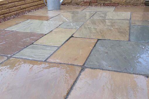 Wet tumbled Raj green in corner of garden patio