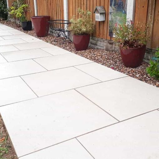 Path laid with vanilla porcelain paving leading through garden next to fence