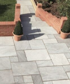 Kandla grey sandstone patio with stairs leading to path surrounded by brick wall