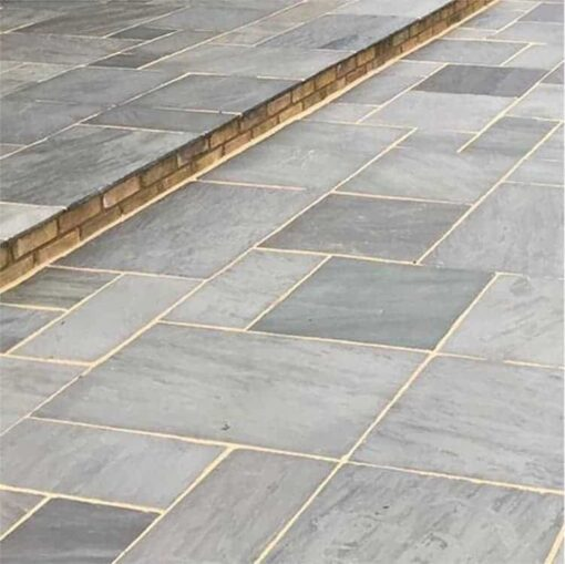 Sagar black sandstone laid in garden patio in front of house