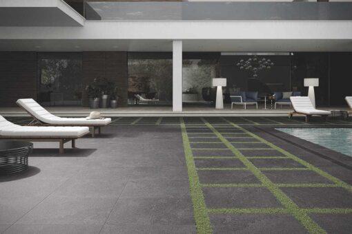 Square slabs of avenue dark grey porcelain laid beside pool