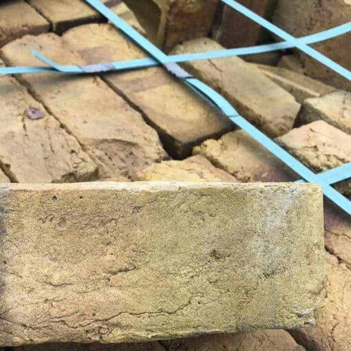 Side of a Funton yellow brick with pallet of Funton yellow bricks behind
