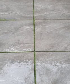 Single size slabs of Anthracite grey porcelain arranged on grass
